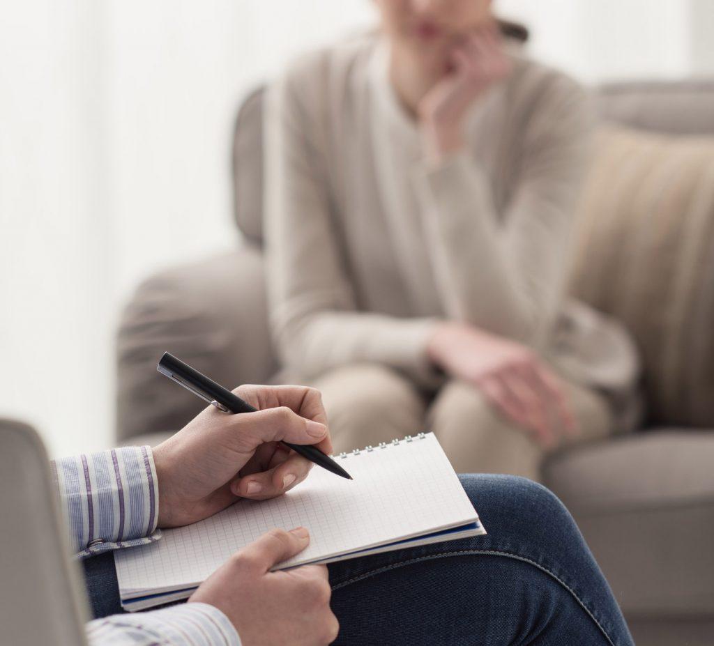 osoba robiąca notatki podczas terapii uzależnień